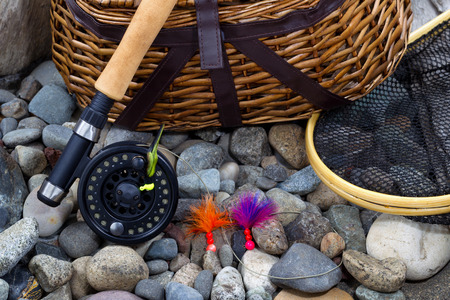 river bed: Top view up of  fishing fly reel, landing net, creel and assorted flies on dry river bed rocks