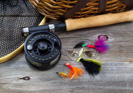 Close up top view of  fishing fly reel, landing net, creel and assorted flies, with partial cork handled pole on rustic wooden boards