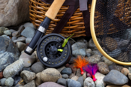 river bed: Close up of  fishing fly reel, landing net, creel and assorted flies on dry river bed rocks Stock Photo