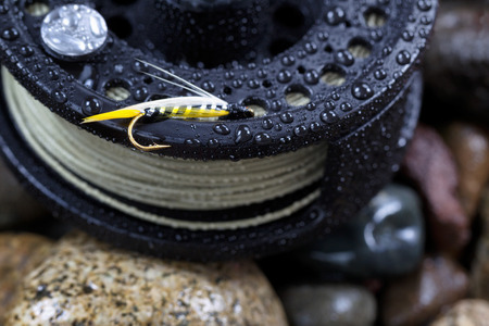 hook up: Close up of single trout fly, focus on golden barbed hook with shallow depth of field, on wet fishing reel with blurred out river rocks in background