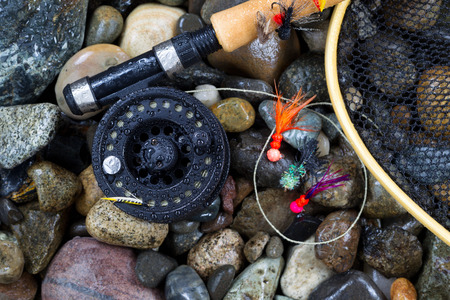 Overhead view of fishing fly reel, landing net and assorted flies on wet river bed stones Stock Photo
