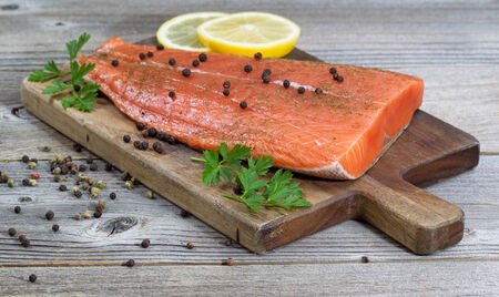 king salmon: Close up of delicious fresh salmon fillet; focus on front, with herbs, spices and lemon slices on rustic wood Stock Photo
