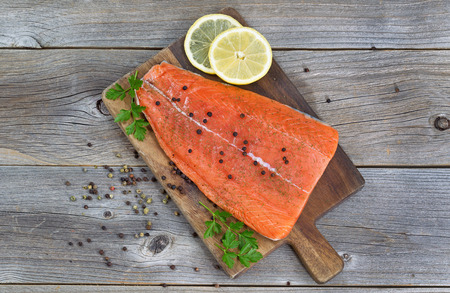 Top view image of a fresh salmon fillet with herbs, spices and lemon slices on rustic wood ready to be cooked.