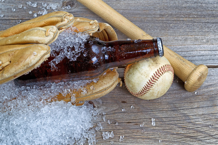 Close up of a brown bottled beer with crushed ice inside of baseball glove on rustic wood with ball and bat