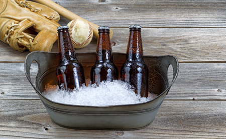 beer bottle: Front view of three brown bottled beers, crushed ice in metal bucket, and baseball equipment in background on rustic wood