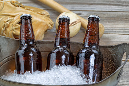 beer bucket: Close up of three brown cold bottled beers, crushed ice in metal container, and baseball equipment in background on rustic wood