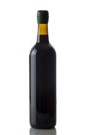 Unopened bottle of red wine, with green cap, on white with reflection