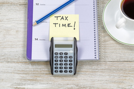 tax law: Horizontal top view of an office wooden desktop with small calendar, calculator, coffee and sharpen blue pencil with reminder of doing Tax Returns.