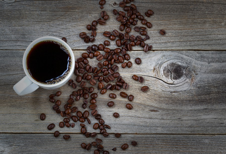 slight: Top view image of fresh dark coffee and premium roasted whole beans on rustic wood with slight vignette border