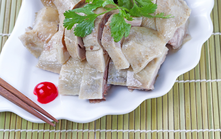 Close up image of Chinese cooked chicken, parsley, cherry and chopsticks on white plate with natural bamboo place mat background photo