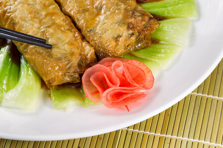 Slightly angled close up of Chinese tofu wrapped meat and vegetables, focus on radish decoration, with natural bamboo place mat background Stock fotó