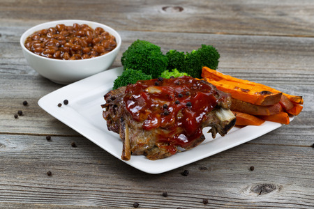 western food: Barbecued spare ribs with yam French fries, broccoli and baked beans on rustic wooden table.