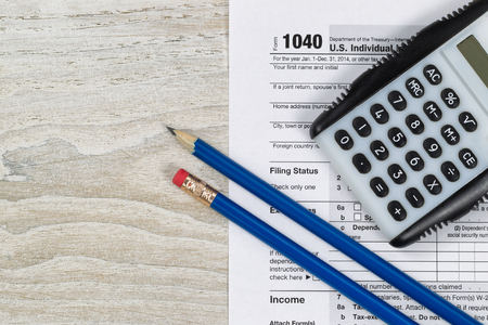 tax law: U.S. Tax form 1040 with calculator and pencils on wooden desktop