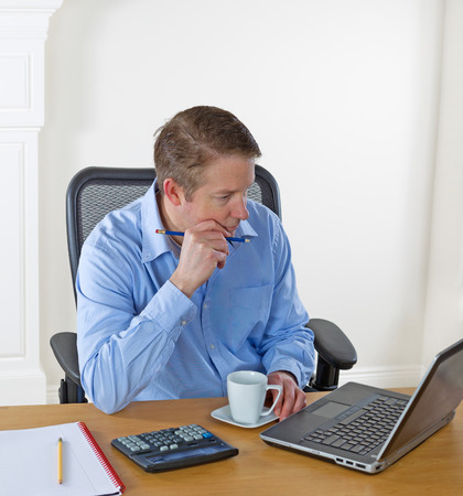 Mature man looking at laptop screen, pencil in hand, while working with white wall in background