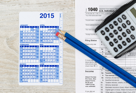 taxation: U.S. Tax form 1040 with calculator, calendar and pencils on wooden desktop Stock Photo