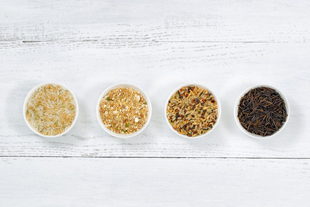 Top view of various rice types each within a small bowl on white wood