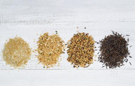 arroz blanco: Vista superior de varios tipos de arroz cada una dentro de una pila individual de madera blanca