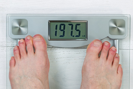 Weight scale, displaying body weight, with bare male feet photo
