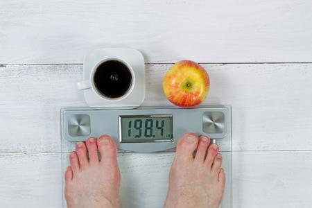 pies masculinos: Escala del peso, mostrando el peso corporal, con los pies desnudos masculinos y la manzana entera con café negro en frente en el piso de madera blanca Foto de archivo