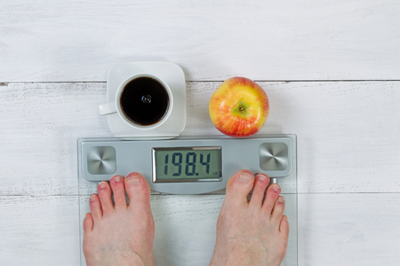 Weight scale, displaying body weight, with bare male feet and whole apple with black coffee in front  on white wooden floor photo