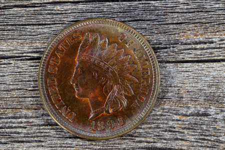 uncirculated: Close up shot of Indian Head Cent, uncirculated condition, on aged wood. Coin showing red and brown colors from copper metal aging process. First one cent that was legal tender by the coinage act of 1864 of the United States. Stock Photo