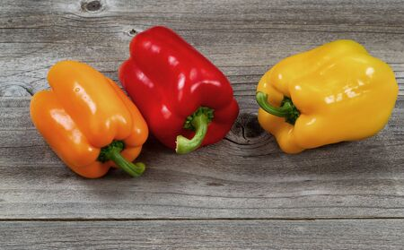 bell peppers: Three fresh bell peppers on aged wood