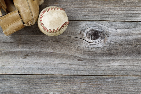 Horizontal top view angle of old baseball and weathered leather mitt on rustic wood