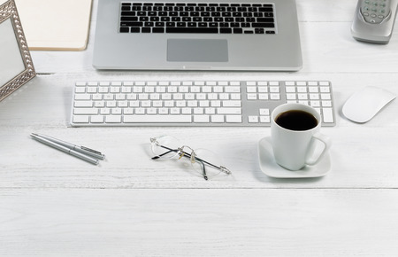 front desk: Front view angle of desktop layout for proper use consisting of laptop, keyboard, pens, mouse, picture frame, phone, coffee, reading glasses and work folders on white desk. Stock Photo