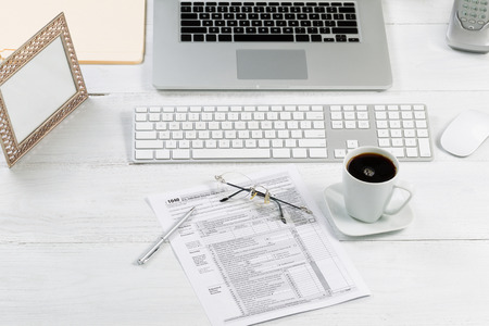 front desk: Front view angle of desktop layout for proper use consisting of laptop, keyboard, pens, mouse, picture frame, phone, coffee, reading glasses, tax forms and work folders on white desk. Stock Photo