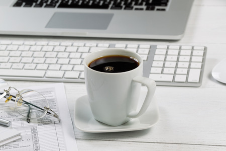 front desk: Close up of a fresh cup of black coffee with laptop, keyboard, pen, mouse, reading glasses and tax forms in background on white desk. Focus on front lip of coffee cup.