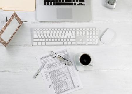 liggande: Top visningsvinkeln för Office Desktop bestående av laptop, tangentbord, pennor, mus, bildram, telefon, kaffe, läsglasögon, deklarationsblanketter och arbets mappar på vitt skrivbord.