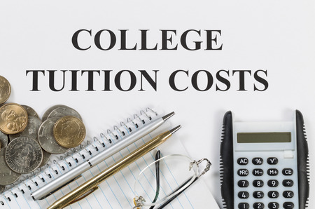 college fund savings: Overhead view of white paper with wording of college tuition costs along with silver and gold pens, calculator, coin money, reading glasses and notebook.