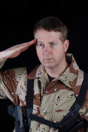 fatigues: Vertical image of military male soldier saluting while armed with black background.