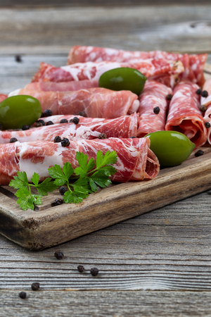 Deli: Close up vertical image of various meats on serving board with ham, pork, beef, parsley, and olives on rustic wood. Focus on front top part of serving board and first row of meat. Stock Photo