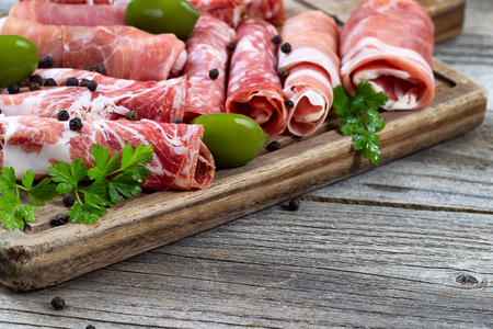 Close up horizontal image of various meats on serving board with ham, pork, beef, parsley, and olives on rustic wood. Focus on side part of serving board and first row of meat. Stok Fotoğraf