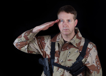 head gear: Horizontal image of military male soldier, head gear removed, saluting while armed with black background. Stock Photo