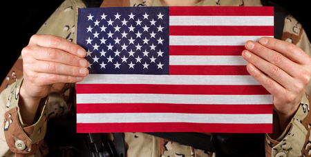 fatigues: Close up horizontal image of United States of America flag with armed male soldier holding it while on black background. Stock Photo