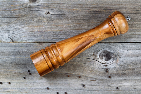 black pepper: Top view shot of Wooden Pepper Mill with whole black pepper spilled on Rustic Wood Stock Photo