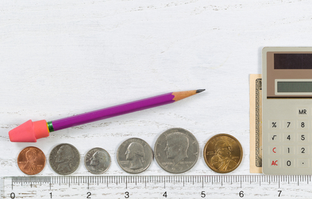 half cent: Clear plastic ruler with coins and money reflecting the concept of measuring investments along with a calculator and pencil with eraser on desktop.