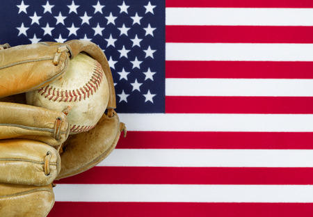 Close up image of worn leather mitt and used baseball with United States of America flag in background. Concept of baseball sport in America. Stock Photo