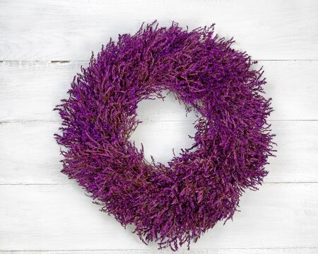 angled view: Top view angled shot of seasonal wreath made of lavender on rustic white wood.