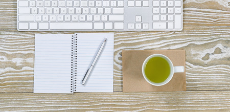 telework: Top view shot of an old white desktop with keyboard, green tea in cup, notepad and pen in horizontal format.