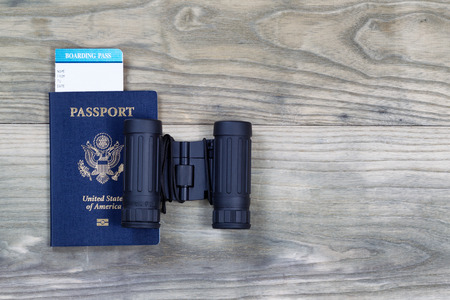 United States passport, boarding pass and binoculars on faded wooden boards.