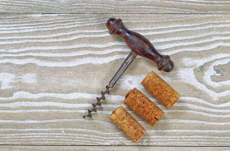 Antique corkscrew with three used corks on rustic wooden boards. Top view angled shot in horizontal format with copy space. photo