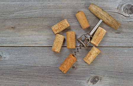 Several used wine corks and opener on rustic wooden boards. Top view angled shot in horizontal format with copy space. photo