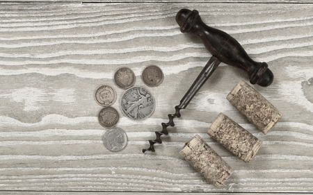 Vintage concept of antique corkscrew with three used corks, old coins on rustic wooden boards. Top view angled shot in horizontal format. photo