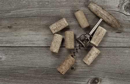 opener: Several used corks and opener on aged cedar wooden boards in vintage style. Top view angled shot in horizontal format with copy space.
