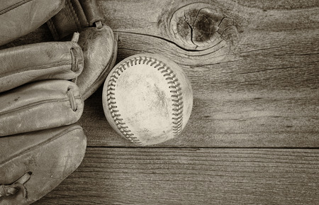 mitt: Vintage concept of old baseball and mitt on rustic wood. Layout in horizontal format. Slight vignette on border.