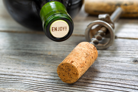 cork screw: Close up shot of top of wine bottle cork, focus on the words enjoy, with rustic opener in background. Horizontal format layout. Stock Photo