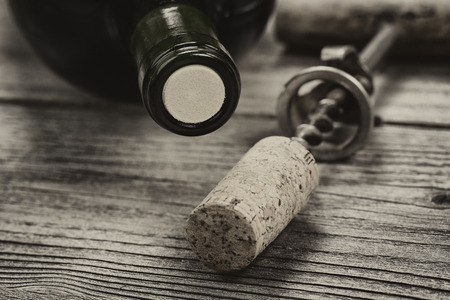 opener: Close up shot of top of wine bottle cork with antique opener in background in vintage style. Layout in horizontal format.